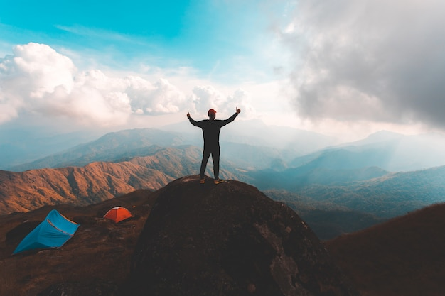 Silueta de hombre levanta la mano en la cima de la montaña, concepto de éxito
