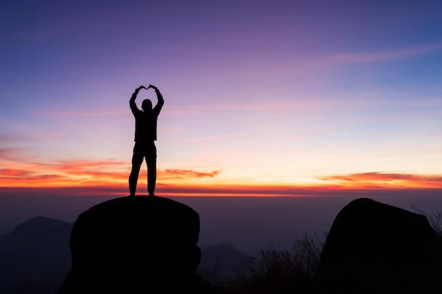 Silueta del hombre levanta las manos en la cima de la montaña, el concepto de éxito