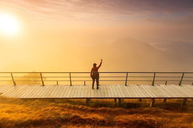 Silueta de hombre levanta las manos en la cima de la montaña, concepto de éxito