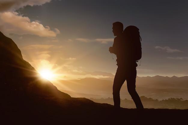 Silueta de hombre mochilero caminando la montaña
