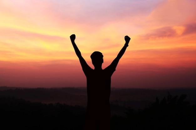 Silueta de hombre mostrar brazo para logros exitosos y celebrar el éxito con salida del sol