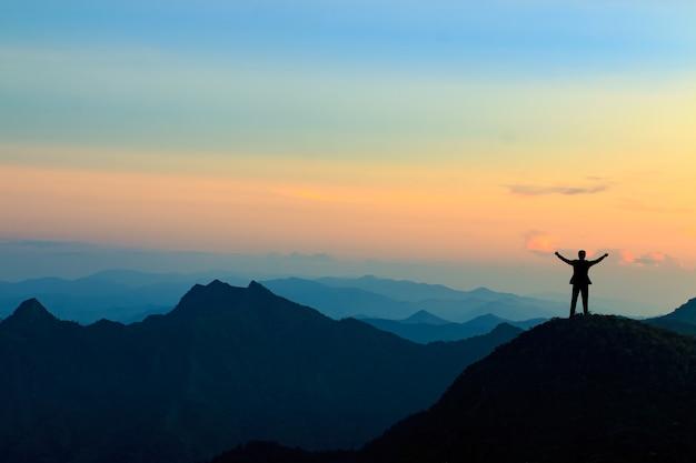Silueta de hombre de negocios en la cima de la montaña sobre fondo de cielo al atardecer, concepto de negocio, éxito, liderazgo y logro