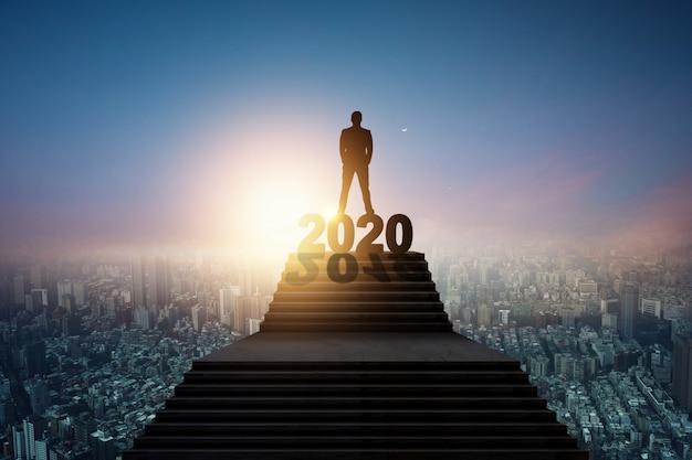 Silueta de hombre de negocios de pie en la escalera y 2020