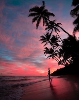 Silueta de un hombre en la playa durante la puesta de sol con increíbles nubes en el cielo rosa