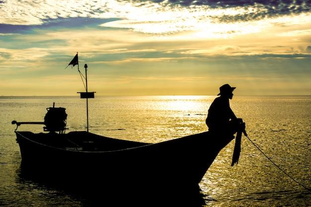 Silueta de un hombre que se sienta en un barco del taxi bajo puesta del sol.