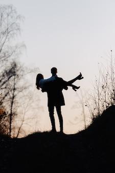 Silueta de un hombre que sostiene a una niña en sus brazos. vista trasera.