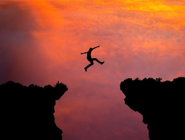 Silueta del hombre saltando por encima del acantilado en el fondo del atardecer