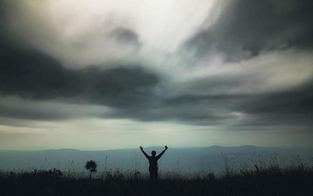 Silueta de hombre solo de pie en la hierba alta en la vista a la montaña con cielo nublado en la naturaleza