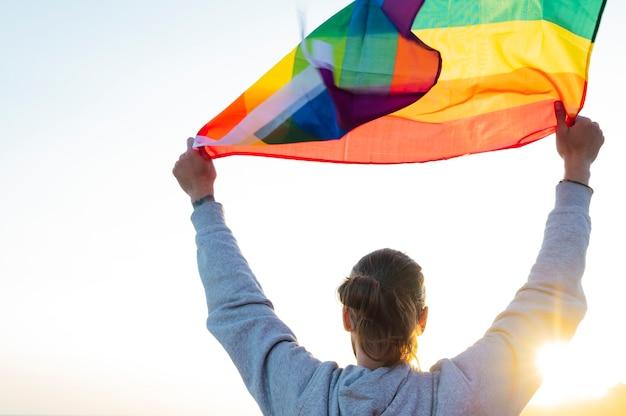 Silueta de un hombre sosteniendo una bandera del arco iris del orgullo gay ondeando al viento en una playa tropical con sol dorado