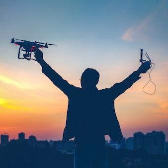 Silueta de hombre sosteniendo encendido drone