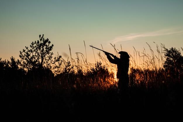Silueta de hunter en un sombrero de vaquero con una pistola en sus manos en una hermosa puesta de sol