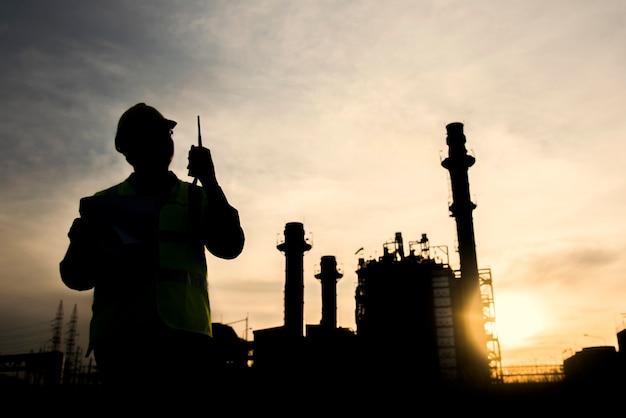 Silueta ingeniero está registrando datos contra el fondo de la planta de energía de ciclo combinado