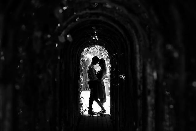 La silueta integral del hombre y la mujer se abrazan en los arcos con las plantas en día soleado. historia de amor. foto en blanco y negro