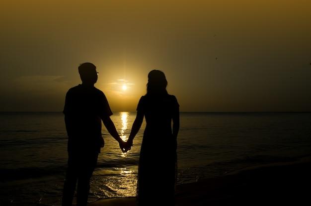 Silueta de una joven novia y el novio en la playa en el fondo del atardecer