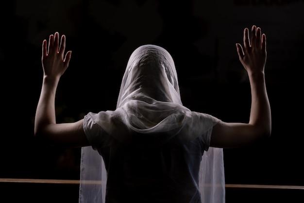 Silueta de una joven que se sienta en la iglesia y rezando con las manos levantadas. vista de primer plano desde atrás. iluminar desde el fondo