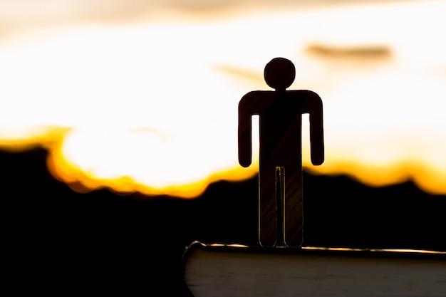 Silueta de la madera del hombre de la muestra que se coloca en el libro de texto en el fondo crepuscular de la tarde de la puesta del sol del cielo,