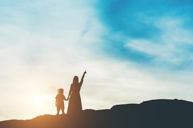 Silueta de la madre con su hija de pie y puesta de sol