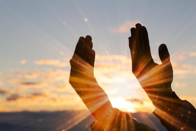 Silueta de la mano del hombre cristiano orando, espiritualidad y religión, hombre orando a dios.
