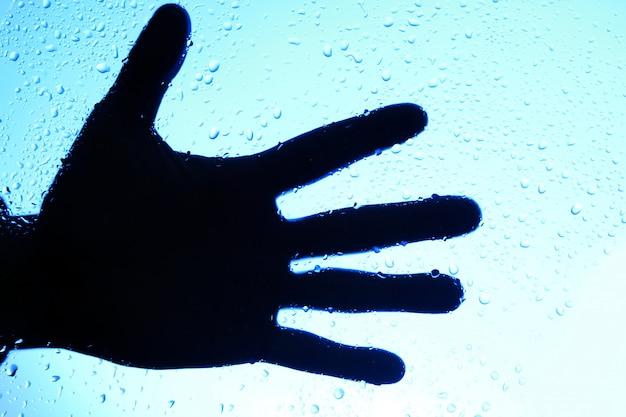 Silueta de mano humana sobre vidrio con gotas