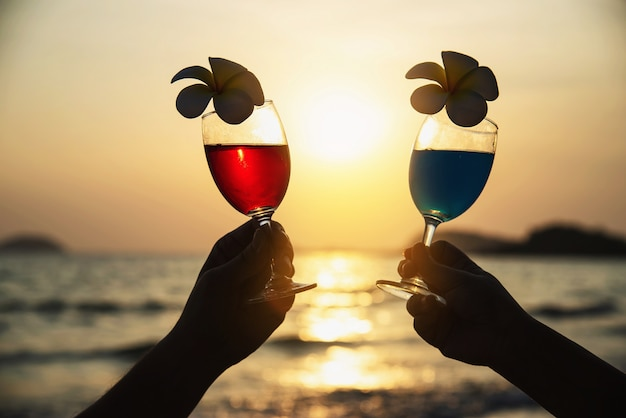 Silueta de la mano de los pares que sostiene la decoración de cristal del cóctel con la flor del plumeria con la playa - feliz relaje las vacaciones de la celebración en concepto del mar