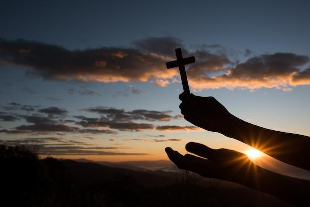 Silueta de mano sostenga cruz de dios