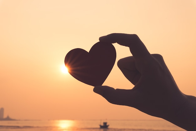 Silueta de mano sosteniendo corazón rojo durante el atardecer de fondo.