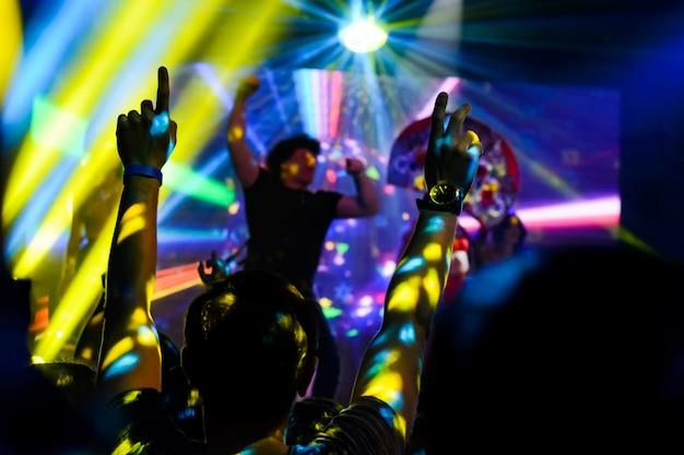 Silueta de manos arriba en el concierto.