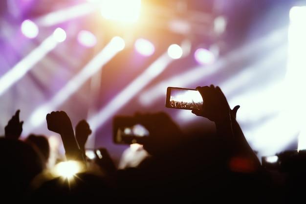 Silueta de manos con teléfono con cámara para tomar fotos y videos en conciertos en vivo