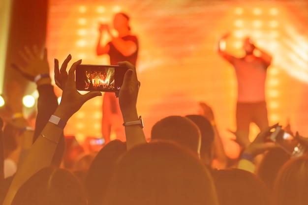 Silueta de manos con un teléfono inteligente en un concierto