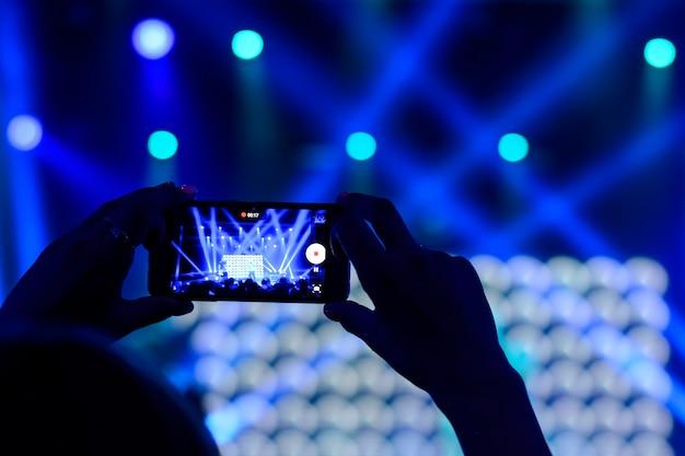 Silueta de manos con un teléfono inteligente en un concierto.