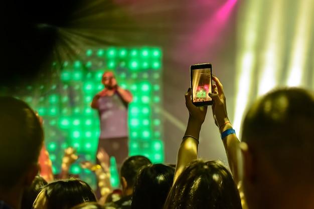 Silueta de manos con un teléfono inteligente en el fondo de los artistas cantantes a la luz de las luces rojas