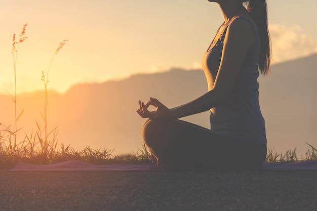 Silueta de la muchacha de la aptitud que practica yoga en la montaña con la luz del sol