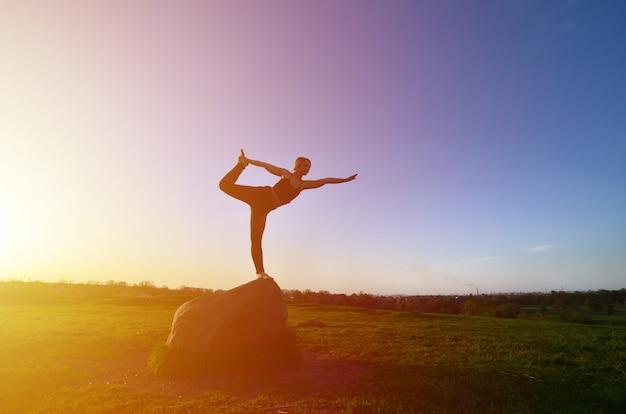 Silueta de la muchacha rubia joven en yoga de la práctica del traje del deporte en una colina verde pintoresca por la tarde en la puesta del sol.