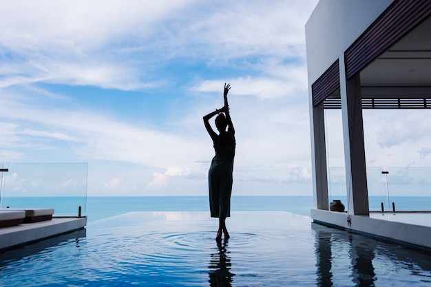 Silueta de una mujer caminando sobre la superficie del agua de la piscina infinita de una costosa villa de lujo rica en una montaña con vista al mar