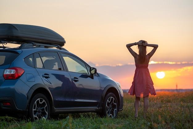 Silueta de mujer conductora de pie cerca de su coche en el campo de hierba disfrutando de la vista de la brillante puesta de sol