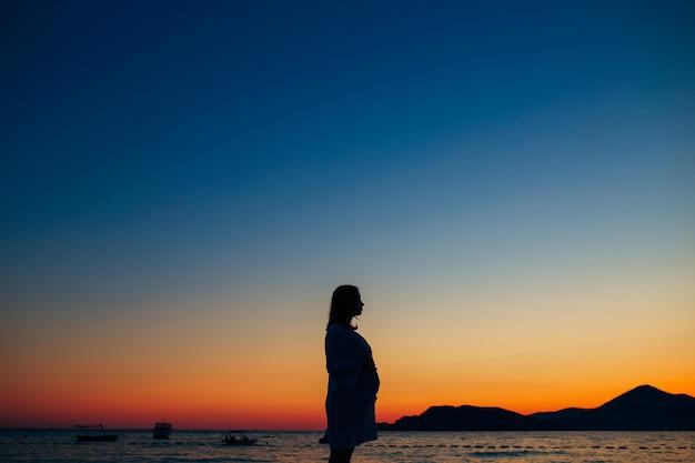 Silueta de una mujer embarazada al atardecer junto al mar