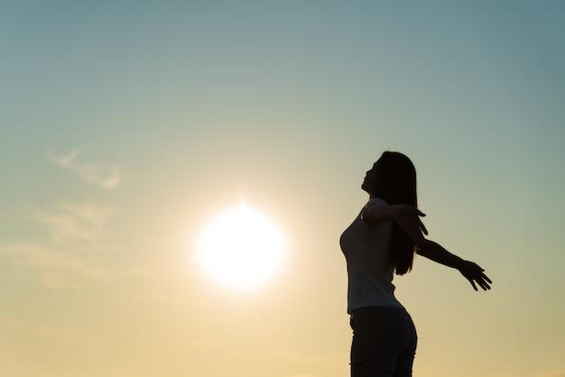 Silueta de mujer extendiendo los brazos, las emociones de libertad.
