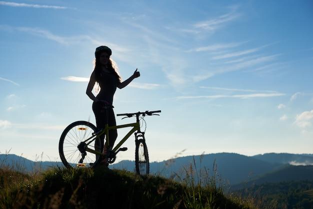 Silueta de mujer feliz ciclista con bicicleta en las montañas, con casco, mostrando los pulgares para arriba en la mañana de verano contra el cielo azul. actividad deportiva al aire libre, concepto de estilo de vida. copia espacio