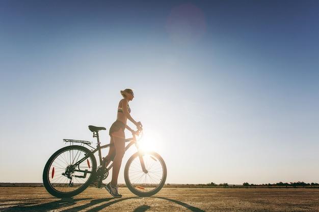 La silueta de una mujer fuerte con un traje de colores que se sienta en una bicicleta en una zona desértica. concepto de fitness.