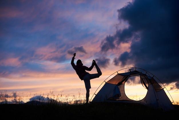 Silueta de una mujer haciendo yoga en la cima de una montaña en la puesta de sol cerca de la tienda