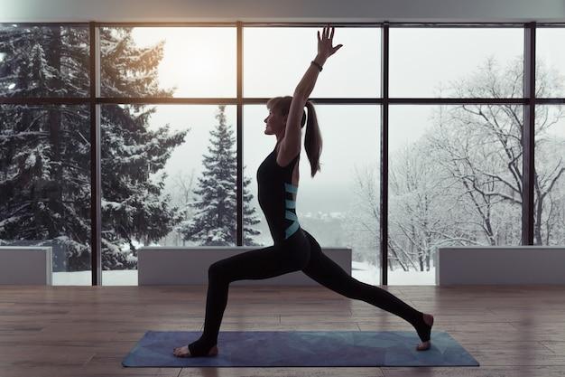Una silueta de una mujer haciendo yoga en el fondo de las ventanas con un hermoso paisaje invernal