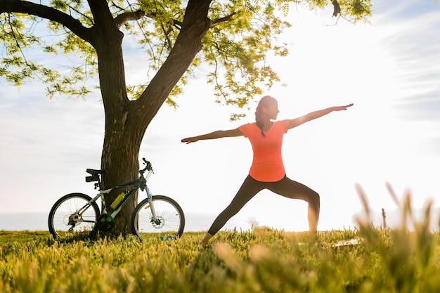 Silueta de mujer hermosa delgada haciendo deporte en la mañana en el parque haciendo yoga