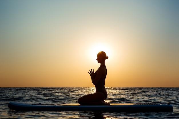 Silueta de mujer hermosa practicando yoga en tabla de surf al amanecer.
