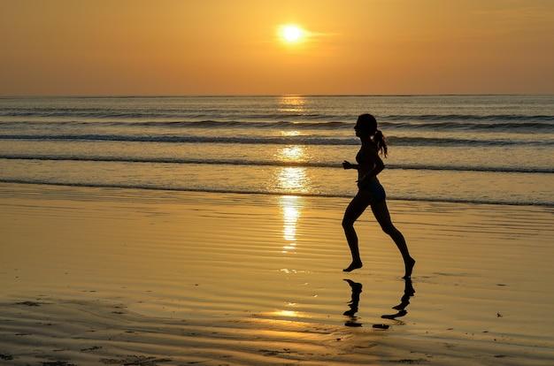 Silueta de mujer jogger corriendo en la playa al atardecer, fitness y concepto de vida saludable