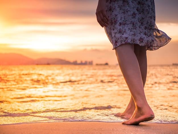 Silueta de mujer joven caminando sola en la playa en la puesta de sol