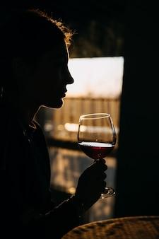 Silueta de una mujer joven con una copa de vino tinto en la luz del atardecer