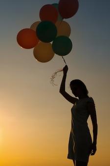 Silueta de mujer joven con globos voladores contra el cielo. concepto de felicidad y sueños