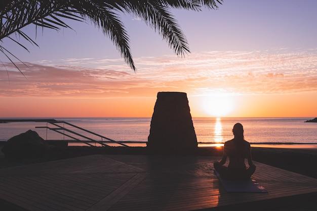 Silueta de mujer joven meditando al amanecer frente a la playa