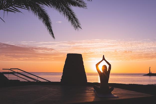 Silueta de mujer joven meditando frente a la playa al amanecer.