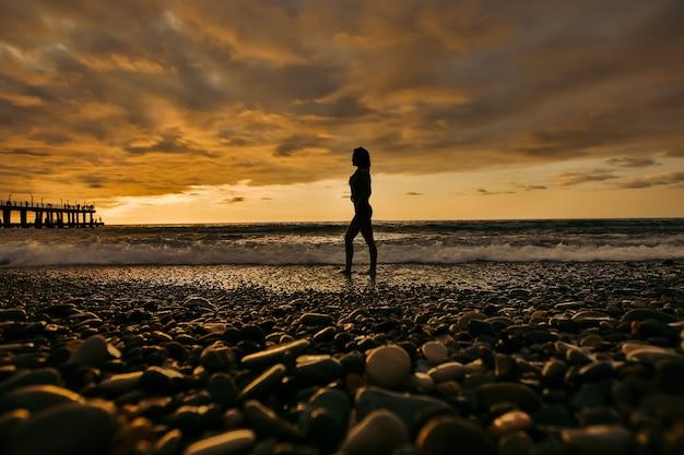 Silueta de mujer joven en la playa de guijarros al atardecer